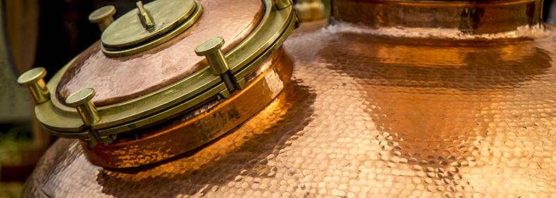 Oude jenever maakt men traditioneel via koperen pot stills